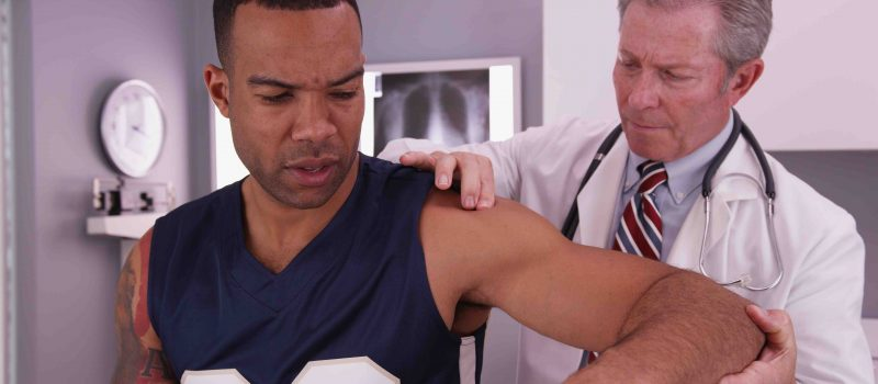 Middle aged male physician treating young male adult athlete's injury.